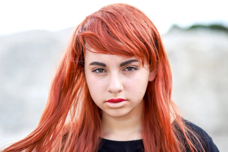 close up of a teenage girl with a red wig