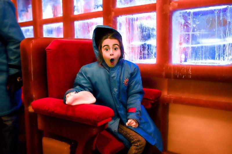 Surprised little girl sitting inside the Polar Express