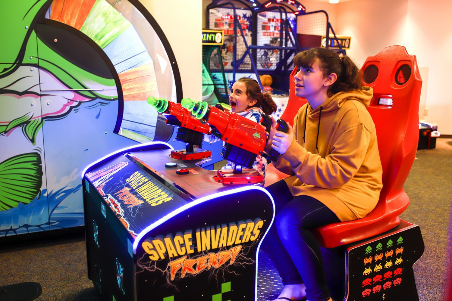 Two girls playing a game at an arcade