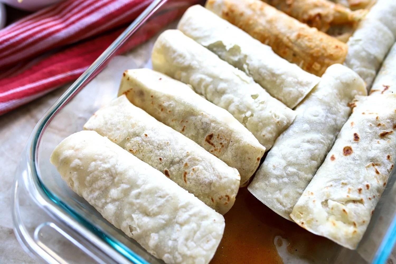 baking dish with rolled up enchiladas