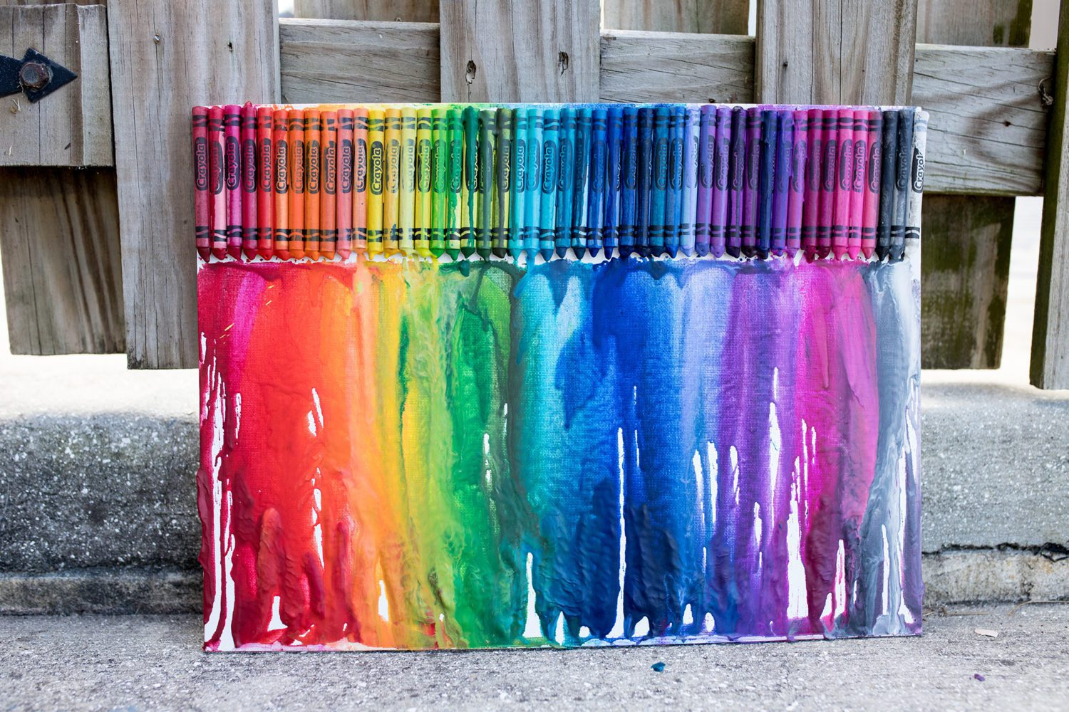 melted crayon art leaning up against a fence
