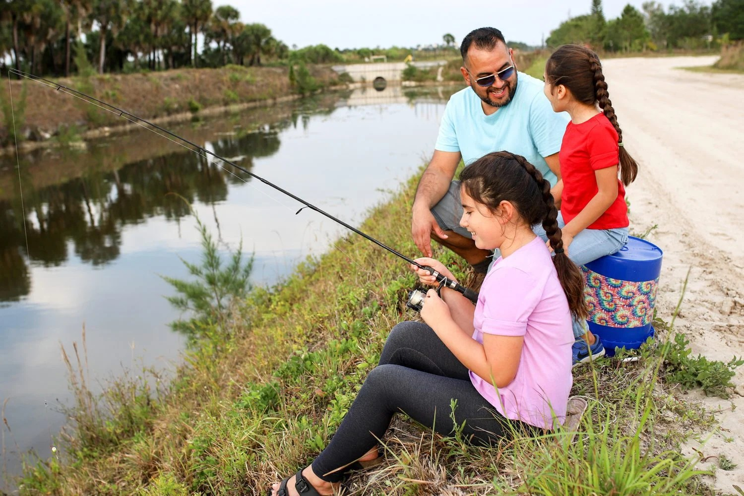 dad fishing with three daughters
