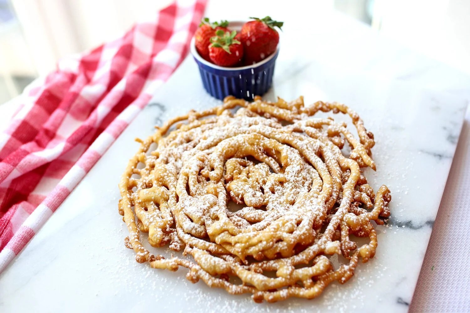 homemade funnel cake and a bowl of strawberries