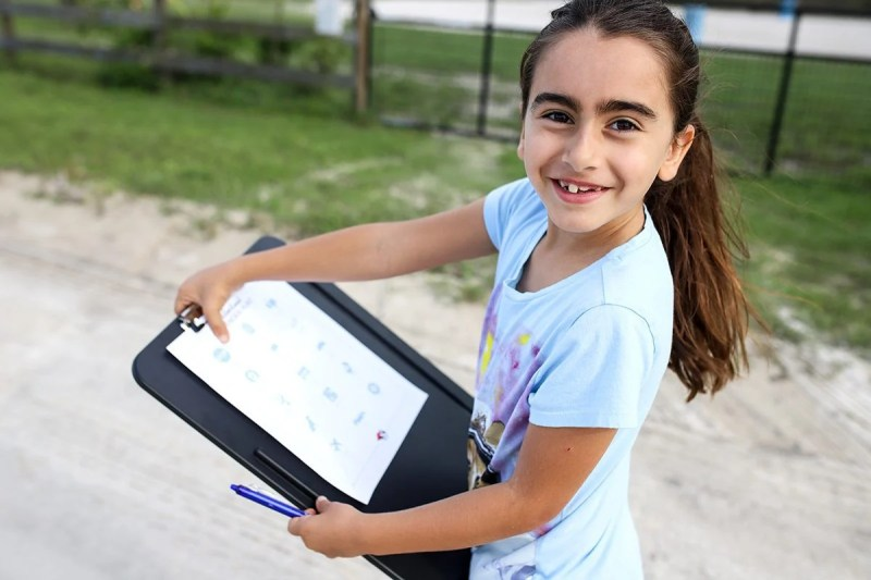 girl holding a lap desk and a printable neighborhood scavenger hunt page