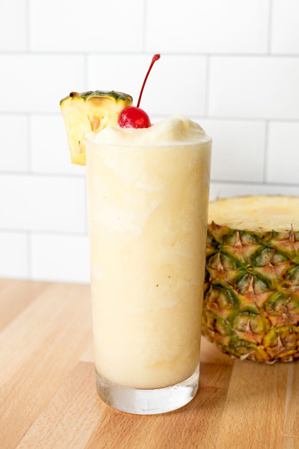 non-alcoholic piña colada with cherry and pineapple garnishes next to a pineapple