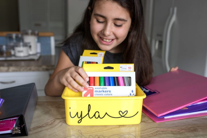 girl reaching into her personalized storage box to pull out markers