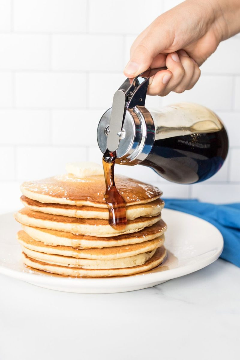 pouring maple syrup on a stack of pancakes