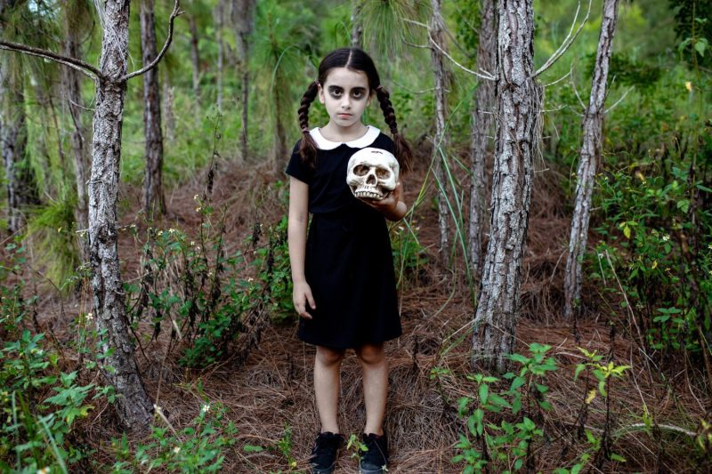 girl dressed as Wednesday Addams holding a skull in the forrest