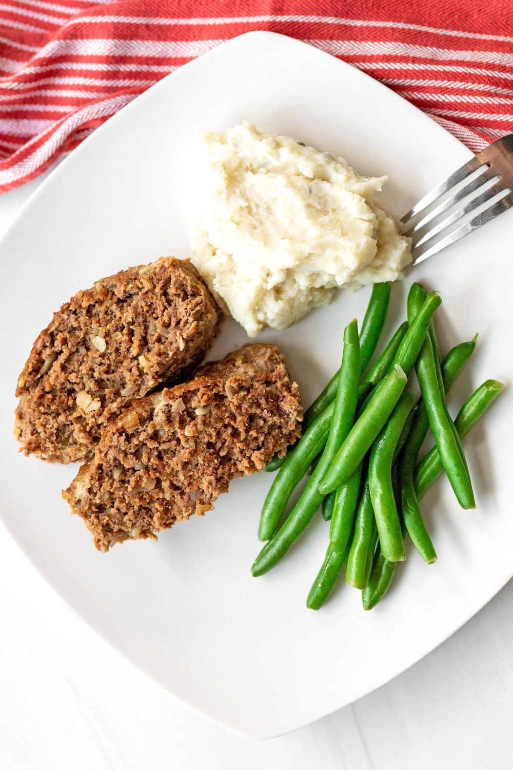plate with meatloaf mashed potatoes and green beans