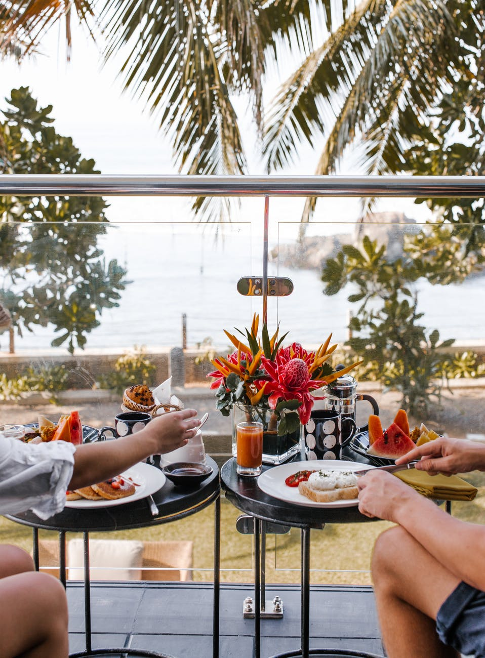 unrecognizable young couple having breakfast on terrace during romantic trip