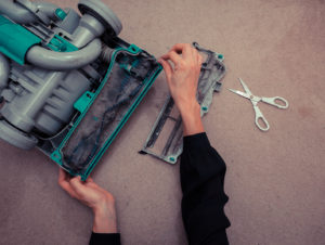 A woman's hands are cleaning and repairing a vacuum cleaner