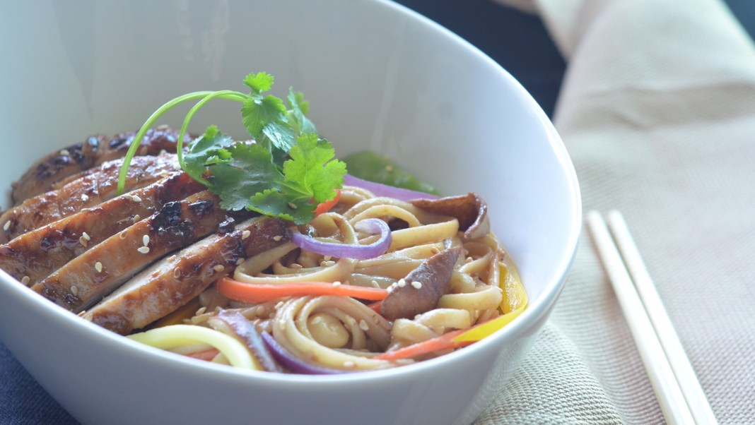 asian noodles with peanut sauce topped with honey glazed chicken