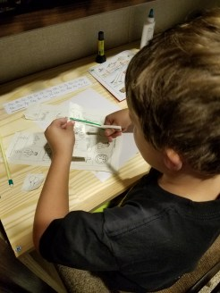 Cutting his pictures for his letter page