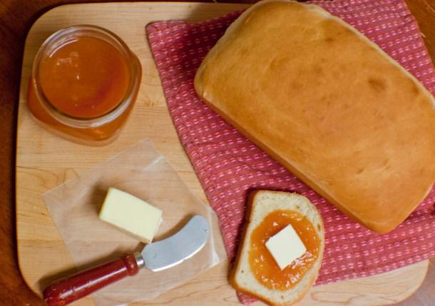 Vista de arriba a un pan de barra casero junto a una barra de mantequilla y un frasco con mermelada