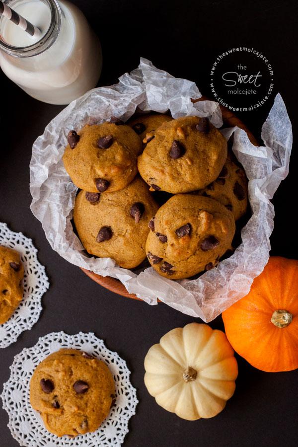 Toma cenital a un plato lleno de galletas de calabaza con chispas de chocolate, hay dos galletitas sobre la mesa, calabazas decorativas y un vaso de leche con popote en blanco y negro
