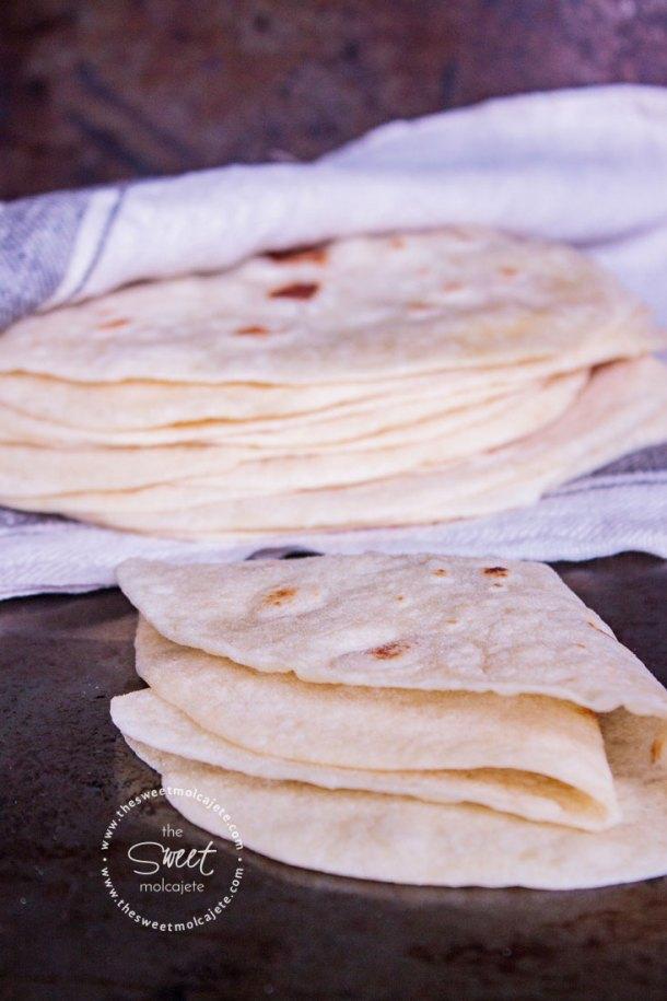 Acercamiento a una tortilla de harina suavecita doblada en cuatro, al fondo se ve un apilo de tortillas de harina