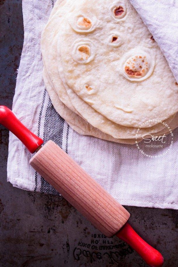 Vista de arriba a varias tortillas de harina apiladas con un rodillo a lado