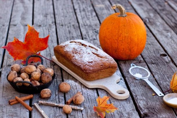 Pan de Zucchini y Calabaza sobre una base de madera rústica, hay una calabaza naranja grande y nueces sobre la mesa