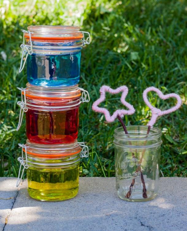Tres frascos con líquido para hacer burbujas, hay dos sopladores de alambre en un frasco a un lado