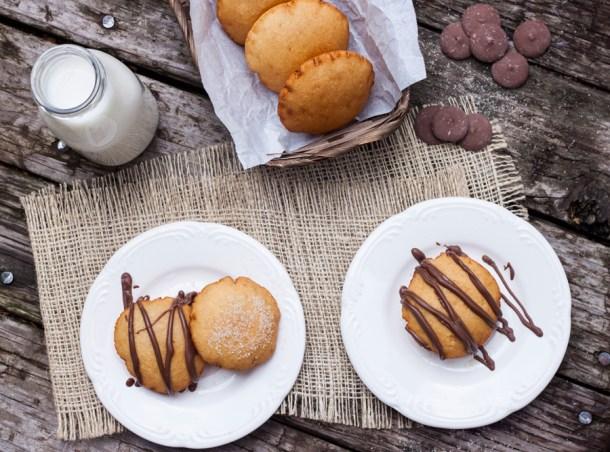 Imagen aérea de Gorditas Dulces de Maíz infladitas sobre platos de cerámica blancos. Hay un frasco con leche a un lado y un canasto con más gorditas del otro