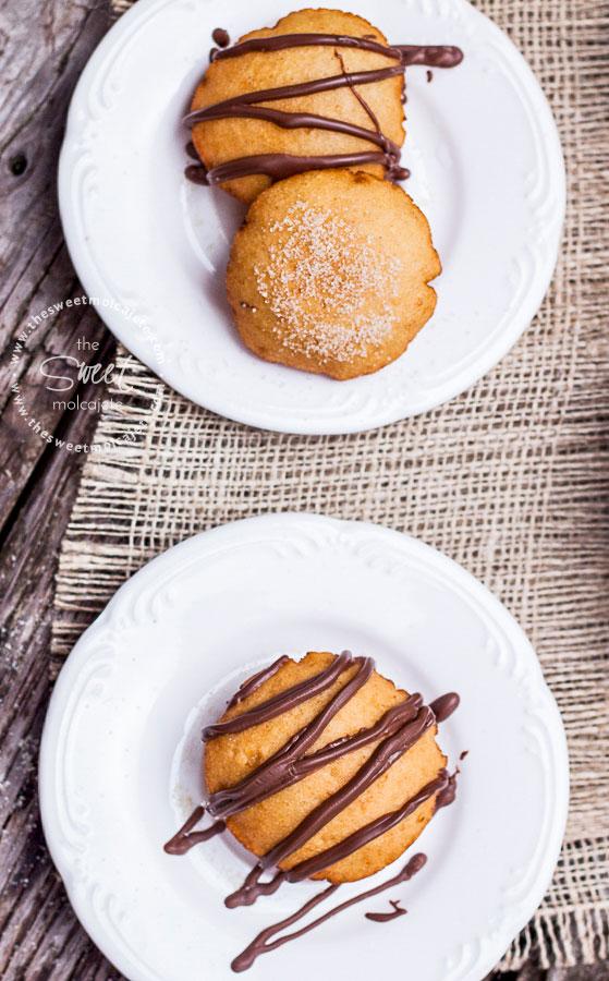 Dos platos con gorditas de maíz dulces con chocolate derretido y azúcar espolvoreada