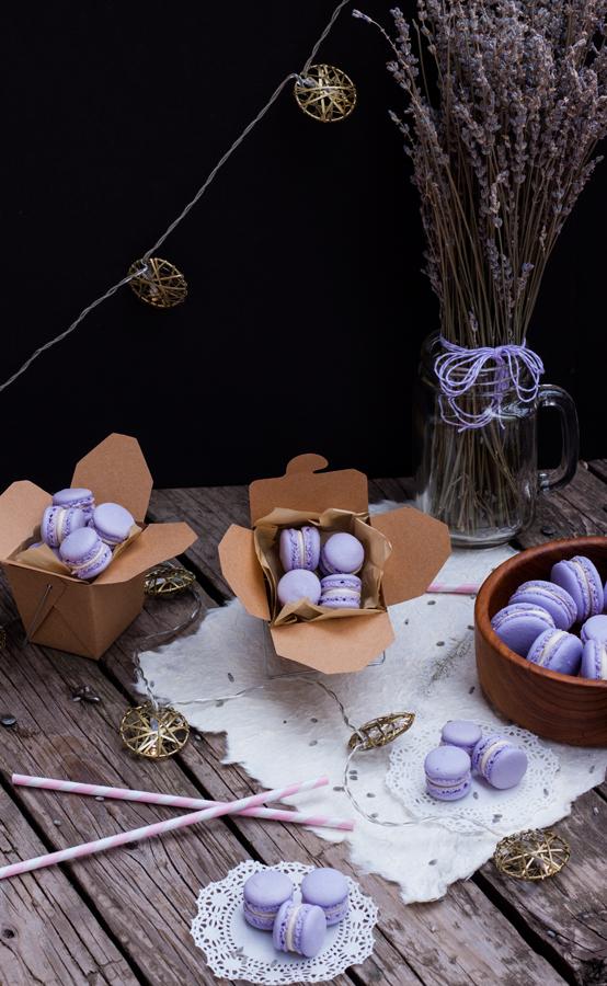 Mesa vintage con cajitas de comida para llevar llenas de mini macarons