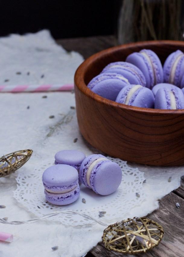 Acercamiento a 3 mini french macarons, al fondo un plato de madera con macarons de tamaño normal