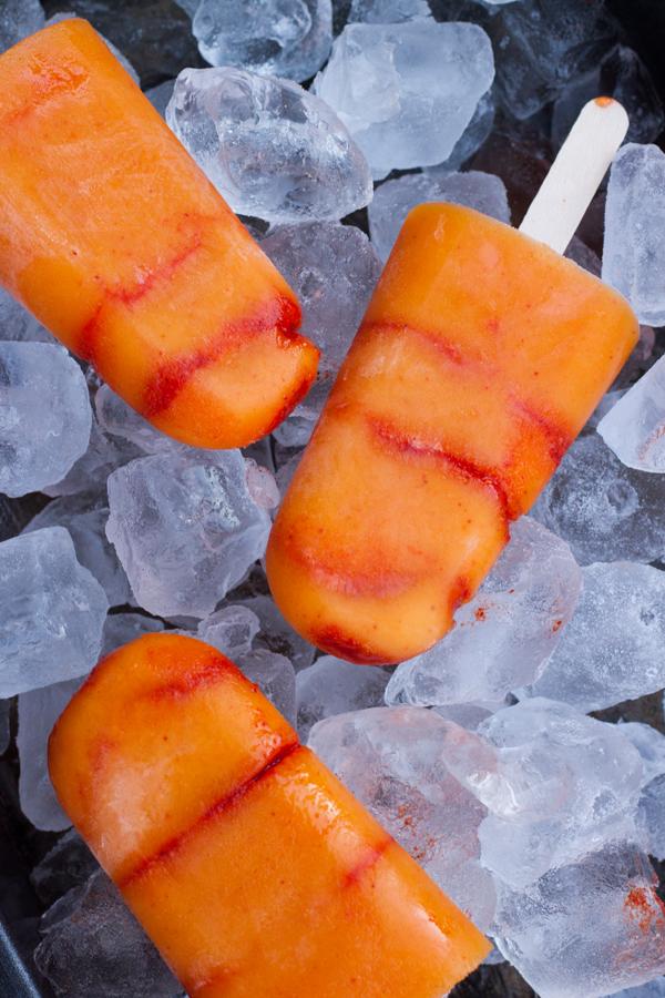 Acercamiento a tres Paletas de Mango con Chile sobre hielo vistas desde arriba