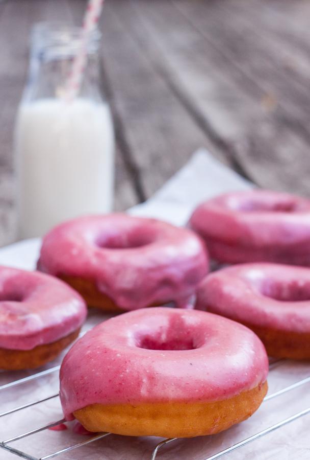 Rejilla llena de donas con un glaseado rosa, al fondo un frasco con leche y popote
