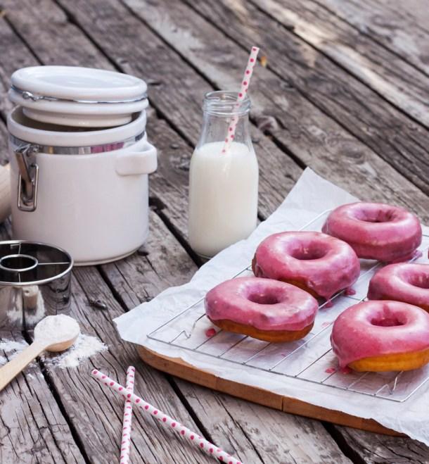 Una mesa con donas glaseadas, un frasco con leche y un recipiente con harina