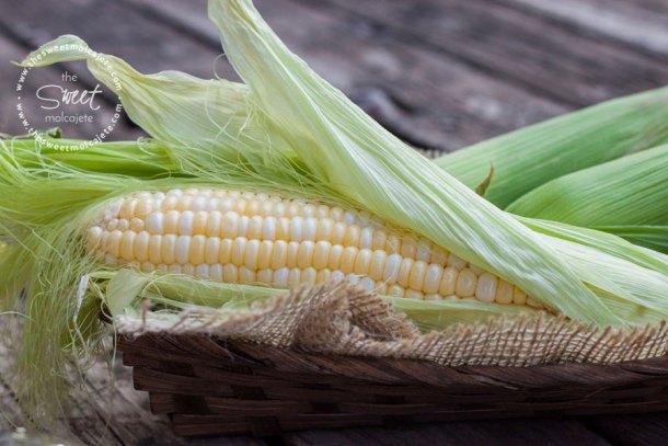 Canasta con una mazorca de maíz blanco, o elote con las hojas medio abiertas