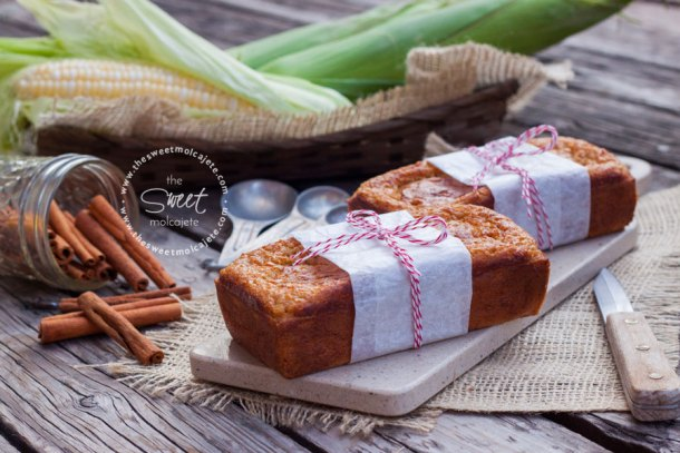 Pan de elote sobre una mesa rústica de madera, al fondo se ven elotes frescos y canela en rajas