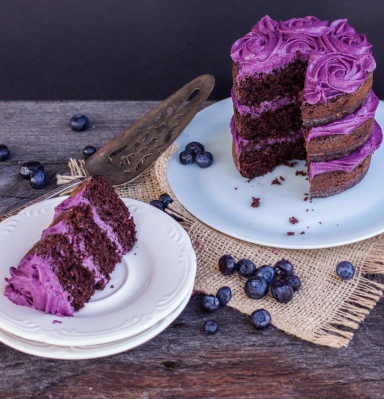 Rebanada de pastel naked de chocolate en tres capas con betún de moras, al fondo se ve el resto del pastel