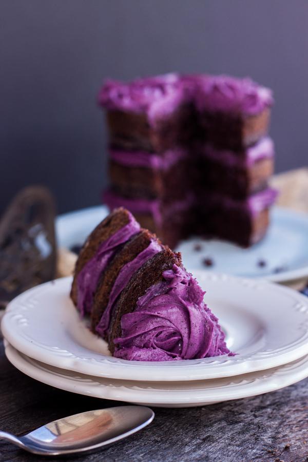 Acercamiento a una rebanada de pastel de chocolate con betún de moras