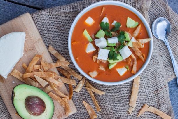 Vista cenital a un plato de sopa de tortilla con cubitos de aguacate, queso fresco y cilantro