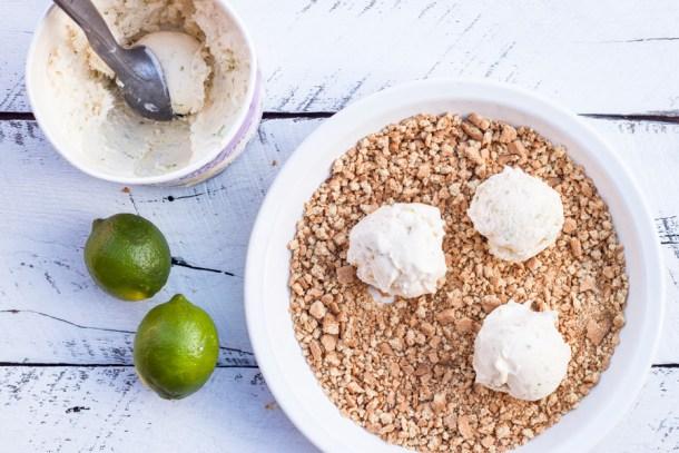 vista de arriba a un bote de helado de yogurt, dos limones persas y un plato con galletas en trozos y 3 bolas de yogurt encima de la galleta
