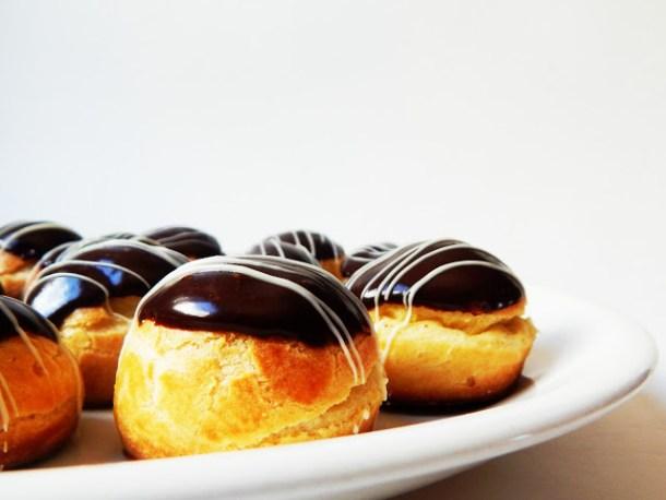 Acercamiento a un plato con profiteroles cubiertos con chocolate y rellenos de crema pastelera para celebrar el Dia del Padre