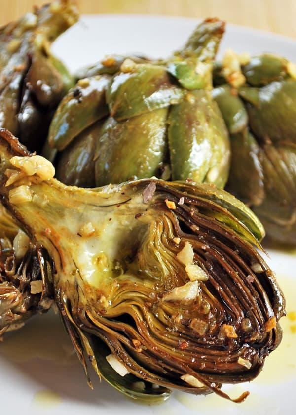Acercamiento a una alcachofa a la mitad asada en aceite con ajo, receta para celebrar el dia del padre