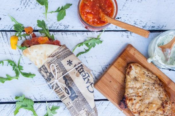 vista de arriba a un gyro de pollo con mango y salsa de habanero, a un lado una tablita con pollo asado