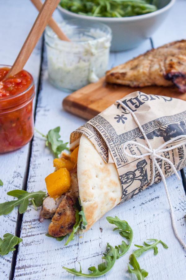 Gyro de pollo con hojitas de arúgula y mango picado, al fondo salsa tzatziki y salsa la victoria