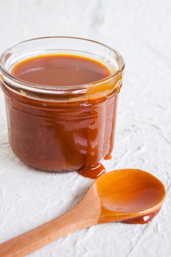 Frasco pequeño con salsa de caramelo salado, con un poco de caramelo escurriendo por un lado del frasco y una cucharita de madera a un lado