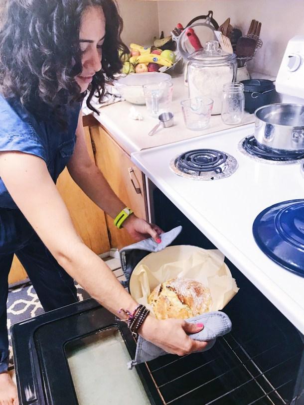 Sacando pan del horno en el Manos a la Masa Workshop: Taller de Panadería Casera