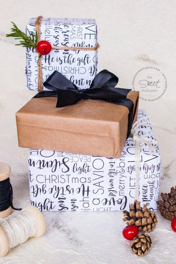 Regalos de Navidad apilados, dos de ellos forrados con una linda envoltura de regalos para Navidad con un diseño en blanco y negro.