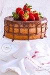 Pastel de mantequilla en tres capas, relleno con buttercream de chocolate y cubierto con un ganache de chocolate que escurre por las orillas. El pastel está cubierto con fresas enteras en la superficie y descansa sobre un cake stand blanco.