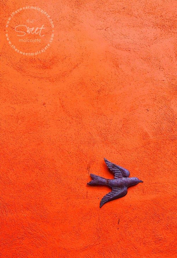 Foto de un pájaro de herrería colgado en una pared naranja intenso - Vida Slow