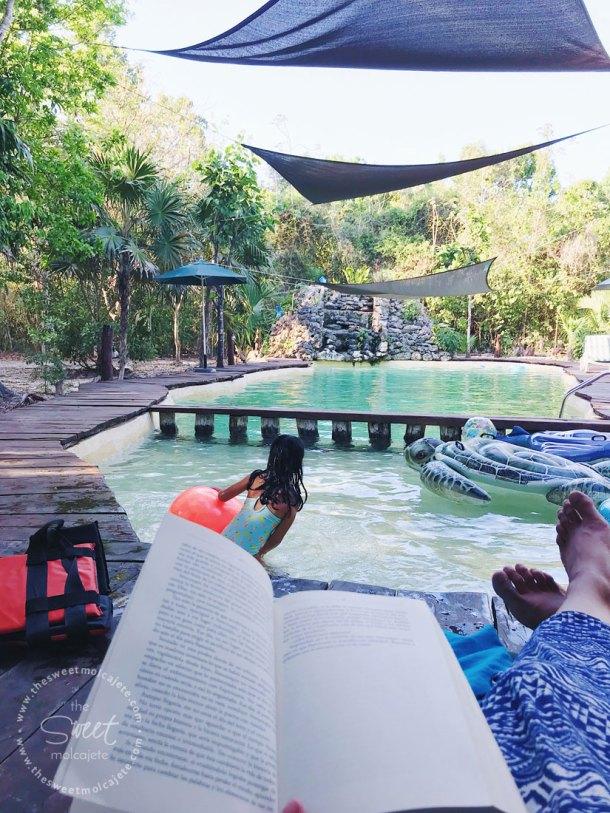 Foto de una mujer leyendo un libro mientras observa a su hija nadando en una piscina en medio de la selva - Vida Slow