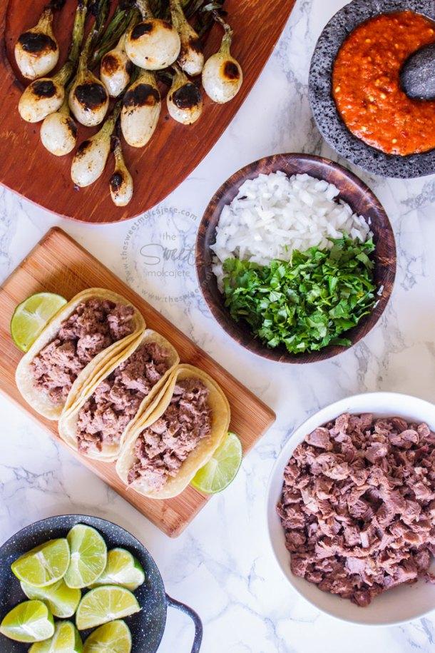 Vista aérea de tres tacos de lengua de res. En la mesa se ve un plato con cilantro y cebolla picados, otro plato lleno de carne de lengua de res picada, limones, cebollitas de cambray y un molcajete con salsa roja.