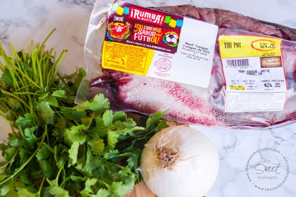 Paquete de Lengua de Res Rumba Meats a lado de un ramo de cilantro y una cebolla entera