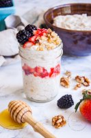 Desayuno de Quinoa con Yogurt en un mason jar, con fresas, zarzamoras y nueces. Se ve una palita de miel al frente junto con nueces y berries alrededor del frasco