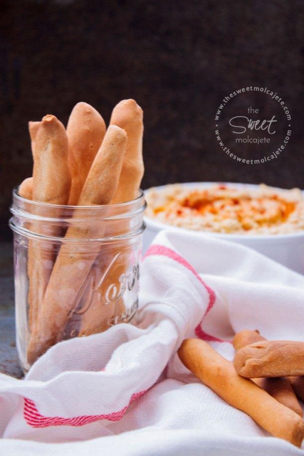 Foto de Palitos de Pan crujientes caseros dentro de un mason jar, una telita blanca alrededor del frasco y un par de palitos sobre ella. Al fondo de ve un recipiente con Hummus casero.